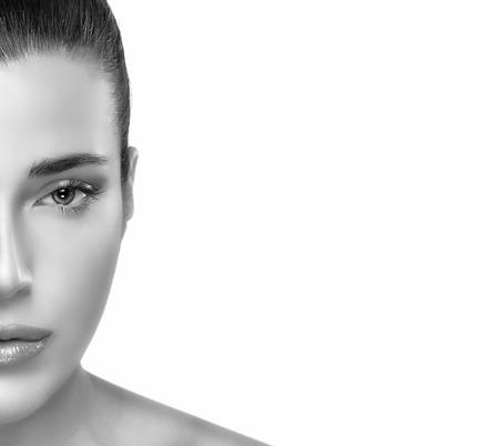 Primo piano metà Flawless volto di giovane donna graziosa nella Monochrome al frame di sinistra, guardando la telecamera, con copia spazio sul lato destro. Bella sana giovane donna con il volto pulito. Pelle perfetta. Ritratto in bianco e nero isolato su bianco