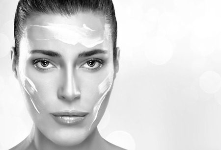 flawless: Beautiful healthy young woman with moisturizer in her clean face, close-up portrait in black and white. Skin care concept. Spa Treatment