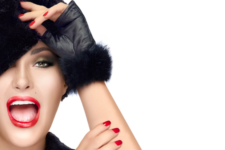 Winter beauty fashion. Close up portrait of pretty young woman with open mouth facial expression, wearing trendy fur hat and mittens. Gestures and grimaces. Professional makeup and manicure. High fashion portrait isolated on white background with copy spa photo