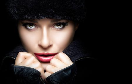 Winter Beauty Fashion. Close-up prachtige jonge vrouw die trendy bont muts en wanten met de handen op de kin, terwijl kijken naar camera sensueel. Geïsoleerd op een zwarte achtergrond. High fashion portret met kopie ruimte voor tekst. Winterse stijl