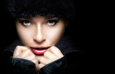 Winter Beauty Fashion. Closeup gorgeous young woman wearing trendy fur hat and mittens with hands on the chin while looking at camera sensually. Isolated on black background. High fashion portrait with copy space for text. Wintry style Standard-Bild