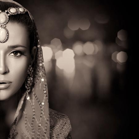 Bellezza etnica Fashion. Bella donna indù con i vestiti tradizionali, gioielli e trucco. Ritratto monocromatico mezza faccia con copia spazio per il testo