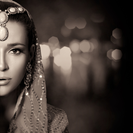 costume jewelry: Ethnic Beauty Fashion. Beautiful hindu woman with traditional clothes, jewelry and makeup. Monochrome half face portrait with copy space for text
