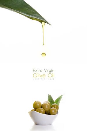 Olio extravergine di oliva sano gocciolante da una foglia verde fresco in una piccola ciotola con semi di olivo. Design Template isolato su bianco con testo di esempio Archivio Fotografico