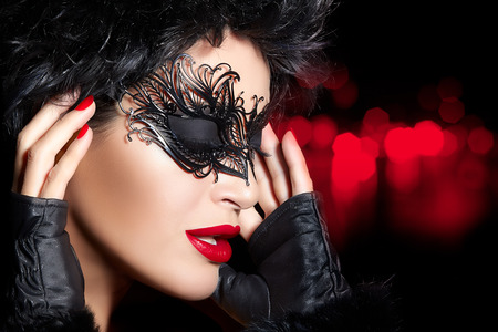 Creative artistic masquerade makeup with dramatic black twirls and tendrils on a gorgeous dark haired woman wearing fashionable gloves, beauty concept profile view with her hands to her hair photo