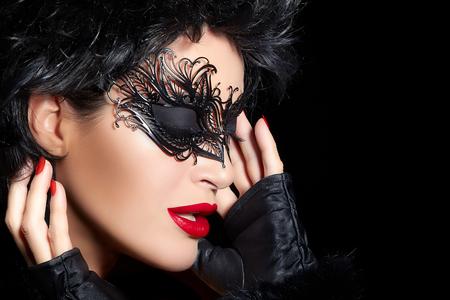 Masquerade. Capelli piuttosto breve splendida donna che indossa elegante maschera nera e guanti alla moda. Sexy labbra e unghie. Bellezza e trucco concetto. Alta moda ritratto isolato su sfondo nero con copia spazio Archivio Fotografico