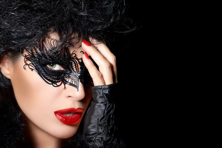 Dark evocative portrait of a glamorous beauty model wearing creative masquerade eye makeup with black detail, closeup face portrait with raised hands in fingerless gloves in a fashion, beauty and makeup concept