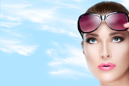 Beauty and Fashion Concept - Closeup Pretty Young Woman Wearing Stylish Red Violet Sunglasses on Forehead, Looking up. High fashion portrait over blue sky with white clouds and Copy Space to the Left photo