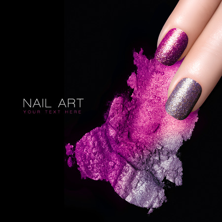 polish: Fingers with silver purple nails and crushed eye shadow with drops of water. Manicure and makeup concept. Closeup image isolated on black with sample text