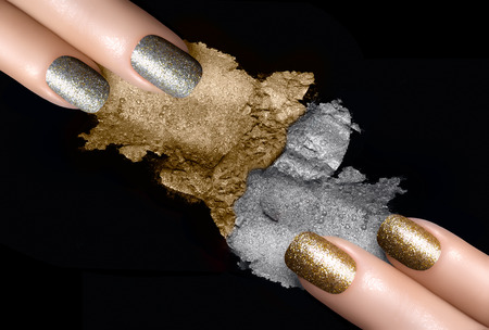 Festive nail art. Fingers with trendy gold and silver nail polish and crushed eye shadow with drops of water. Manicure and makeup concept. Closeup image isolated on black