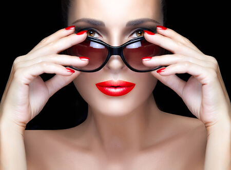 Beautiful fashion model girl with hands on stylish black sunglasses looking at camera. Bright makeup and manicure. High fashion portrait isolated on black background. Beauty and fashion concept. photo