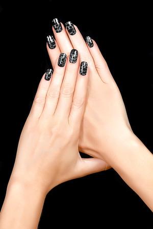 unas largas: Nail Art. Esmalte de u�as crujido de moda en negro. Manicura con u�as y tendencia del tatuaje. Primer plano de manos de la mujer aisladas sobre fondo negro Foto de archivo