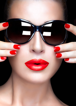 Beautiful fashion model girl with stylish oversized black sunglasses. Bright makeup and manicure. High fashion portrait isolated on black background. Beauty and fashion concept. photo