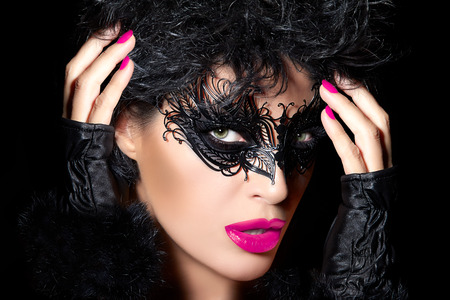 ojos hermosos: Mujer modelo atractiva en el maquillaje de ojos mascarada creativa con detalles de negro, de cerca retrato de la cara con las manos levantadas en los guantes sin dedos en un concepto de moda, belleza y maquillaje