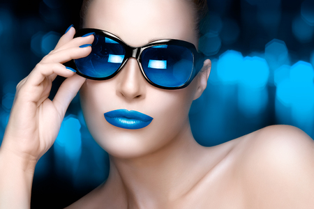 Beautiful fashion model girl with Hand on her stylish oversized sunglasses looking at camera. Colorful makeup and manicure. High fashion portrait over blue and black bokeh background. Beauty and fashion concept. photo