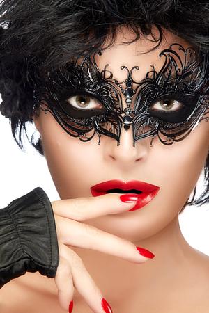 Belleza de la cara de la mujer del primer con la máscara del carnaval elegante negro. Los labios y la manicura rojos. Modelo de la belleza atractiva que desgasta maquillaje creativo del ojo mascarada