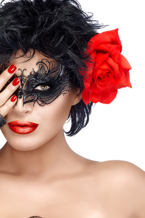 eye mask: Beauty model girl with stylish black carnival mask and Big Red Rose Flower. Red Lips and Manicure. Glamorous beauty model wearing creative masquerade eye makeup. Closeup portrait isolated on white with copy space for text.