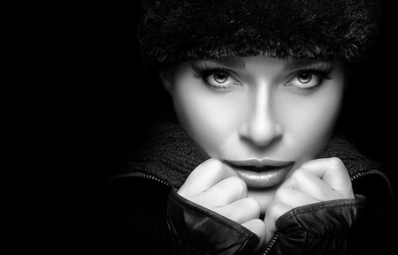 russian hat: Winter Beauty Fashion. Closeup gorgeous young woman wearing trendy fur hat and mittens with hands on the chin while looking at camera sensually. Isolated on black background. Monochrome high fashion portrait with copy space. Wintry style