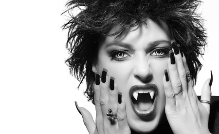 Attractive female vampire with light colored evil eyes snarling at the camera in a gothic concept. Closeup black and white portrait with copy space for text