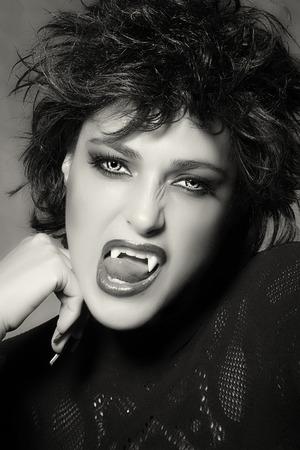 b�se augen: Schwarzweiss-Portrait eines attraktiven weiblichen Vampir mit hellen b�sen Augen entbl��te ihre Z�hne in die Kamera in einem Halloween-Konzept Lizenzfreie Bilder