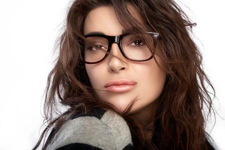 ゴージャスなブルネット ファッション流行のメガネを身に着けているカジュアルなスタイルでモデルの女の子。コピー スペースと白い背景で隔離の