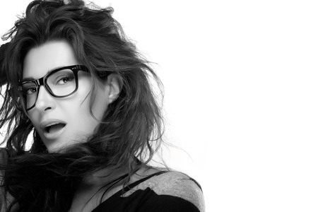 tousled: Close up attractive model woman face with casual hairstyle, wearing fashion eyeglasses while looking at camera. Cool trendy eyewear portrait in Black and White. Isolated on White Background with Copy Space for Text