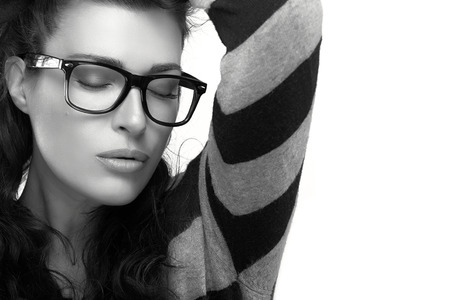 Close up gorgeous brunette fashion model girl with casual style clothing wearing trendy glasses, Holding her hair with closed eyes. Cool trendy eyewear portrait in black and white. isolated on white background with copy space for text