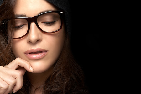 Close up Pretty Young Woman Face, with Glasses, Looking Down with One Hand on the Face. Gorgeous Brunette Fashion Model Girl. Cool Trendy Eyewear Portrait with copy space