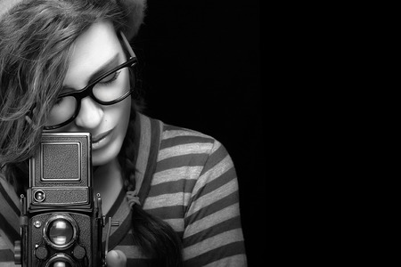 Close up Attractive Young Woman in Trendy Outfit Capturing Photo Using Vintage Camera. Black and White Portrait Isolated on Black Background with Copy Space for Text. Archivio Fotografico
