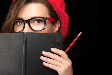 Close up Beauty Stylish College Girl with Expressive Eyes in Trendy Eyeglasses Covering her Face with Black Notebook While Holding a Pencil. Isolated on Black Background with Copy Space for Text