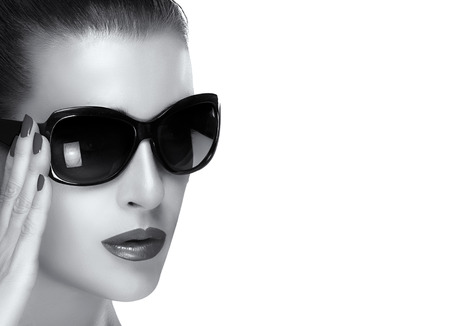 Beautiful fashion model girl with stylish oversized black sunglasses. Closeup face portrait with raised hand to the right of the glasses. High fashion black and white portrait isolated on white with copy space. photo