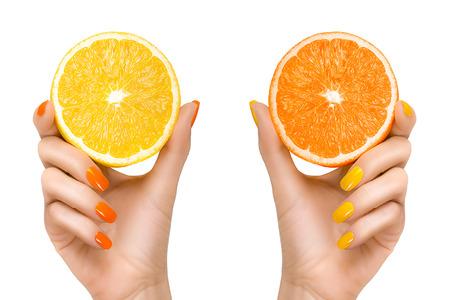 Stijlvolle vrouw handen met oranje en geel gekleurde nagels bedrijf plakjes van citrusvruchten. Close-up geïsoleerd op een witte achtergrond. Gezonde voeding concept