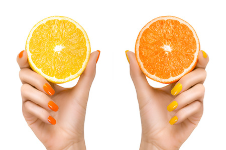 nails manicure: Stylish woman hands with orange and yellow colored nails holding slices of citrus fruits. Close up isolated on white background. Healthy diet concept Stock Photo