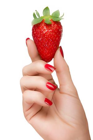 manicura: Cierre de mano femenina con uñas muy cuidadas con esmalte de uñas rojo que sostiene una fresa madura deliciosa en la adecuación del tono de color en un concepto de dieta saludable, aislado en fondo blanco