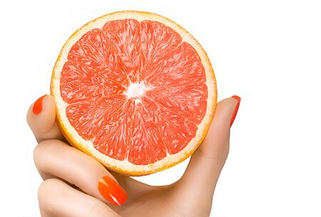 nails: Female hand with pretty manicured nails with orange nail varnish holding a luscious grapefruit in matching color tone in a healthy diet concept, isolated on white with copy space for text Stock Photo