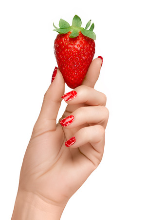 Woman hand with red manicured nails holding up a succulent ripe red strawberry in matching shades of color in a Nail Art and Food concept, isolated on white background.