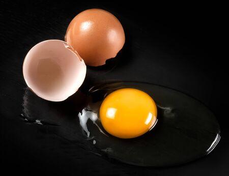yolk: Raw Egg with Yellow Yolk and Broken Shell Halves on black background Stock Photo