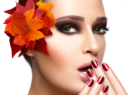 Trendy autumnal makeup and nail art. Fashion beauty model girl. Professional fall fashion makeup and manicure. Closeup portrait isolated on white with copy space