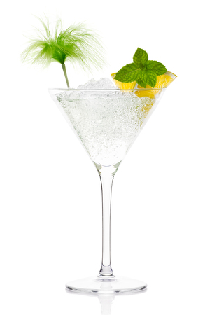 Mojito cocktail with vodka garnished with lemon and mint in a tall stemmed conical martini glass with ice conceptual of a tropical vacation, nightclub or celebration over a white background photo
