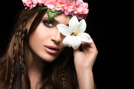 dark haired woman: Beauty in spring concept. Gorgeous dark haired woman holding a spring lily over one eye wearing a headband of pink flowers and trend braids hairstyle. Beauty fashion portrait isolated on black