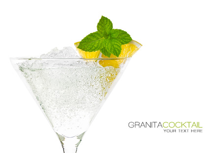 Close up granita cocktail garnished with lemon and mint in a tall stemmed conical martini glass with ice conceptual of a tropical vacation, nightclub or celebration over white background. Template design with sample text photo