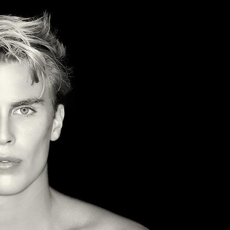 modelos masculinos: Apuesto joven sobre fondo negro. Piel perfecta. Cuidado de la Piel y el concepto de cuidado del cabello. Media cara Retrato del hombre