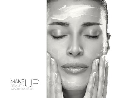 그녀의 깨끗한 얼굴에 로션을 적용 근접 촬영 아름 다운 건강 한 젊은 여자. 스킨 케어 개념입니다. 스파 트리트먼트. 샘플 텍스트 템플릿 디자인