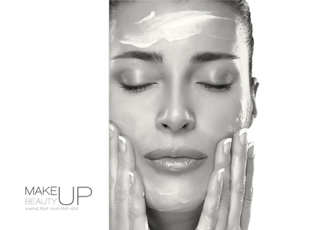 Closeup beautiful healthy young woman applying moisturizer in her clean face. Skin care concept. Spa Treatment. Template design with sample text