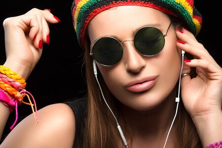 dancing club: Feeling the Music. Close up Fashionable Young Woman Wearing Rastafarian Hat Trendy Round Sunglasses and Colorful Bracelets Enjoying Party Music Through Headphone. Portrait Isolated on Black.