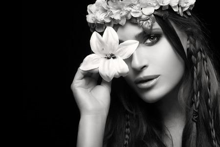 ojos hermosos: Belleza en concepto de primavera. Hermosa mujer de pelo oscuro que sostiene un lirio de primavera sobre un ojo con una corona de flores y peinado de trenzas tendencia. Monocroma Retrato de la belleza aislado en negro con copia espacio para el texto Foto de archivo