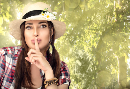 hushing: Close up Hipster Young Pretty Woman in a Hushing Gesture While Looking at the Camera. Spring fashion portrait with copy space. Stock Photo
