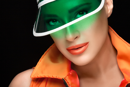 collared shirt: Sports fashion portrait. Close up Gorgeous Woman Face in Green Transparent Plastic Sun Visor and Orange Collared Shirt Looking at Camera Isolated on Black Background. Stock Photo