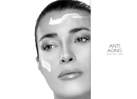 aging: Anti Aging and beauty concept with a monochrome portrait of a gorgeous woman with cosmetic cream on her cheek and forehead and blank copyspace alongside with sample text. Spa treatment. Template design