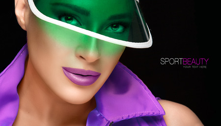 collared shirt: Sport Beauty. Sporty Young Woman in Green Plastic Sun Visor and Violet Collared Shirt Looking at the Camera. Fashion Portrait Isolated on Black Background with Sample Text. Stock Photo